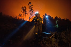 Galicia, Spain: Firefighters work to extinguish the flames during a forest fire in the Entrimo municipality, near Ourense