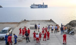 Members of the Italian Red Cross gather on the quay as a quarantine ship makes its way to the port of Lampedusa Island