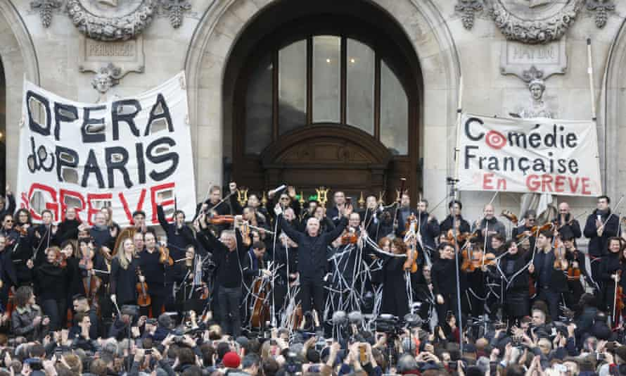 Striking opera musicians wave to the crowd after performing outside the Palais Garnier opera house.