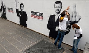 Reporters Without Borders activists paste up posters of presidents Putin, Xi and al-Assad. Press freedom deteriorated in 2015, the group says.