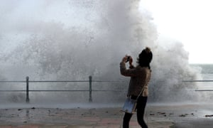 A woman takes a photograph as waves crash on to Penzance seafront on Monday. The disruption from Ophelia continued on Tuesday for parts of northern England and Scotland.