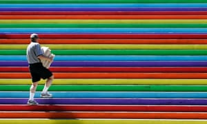 A city hall employee walks up a flight of stairs painted in rainbow colours in Vancouver