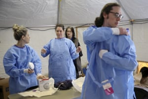 Philadelphia Medical Reserve Corps volunteers put on their protective outfits with the help of Dr. Felicia Lewis, a Philadelphia Department of Public Health medical epidemiologist, as the city's coronavirus testing site prepared to open in South Philadelphia.