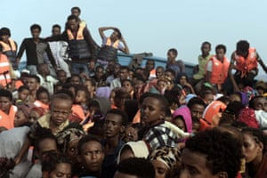 Refugees and migrants wait to be rescued