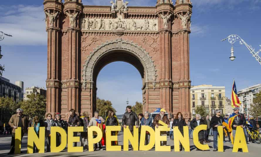 A group of people forms the word independence in large letters in Barcelona