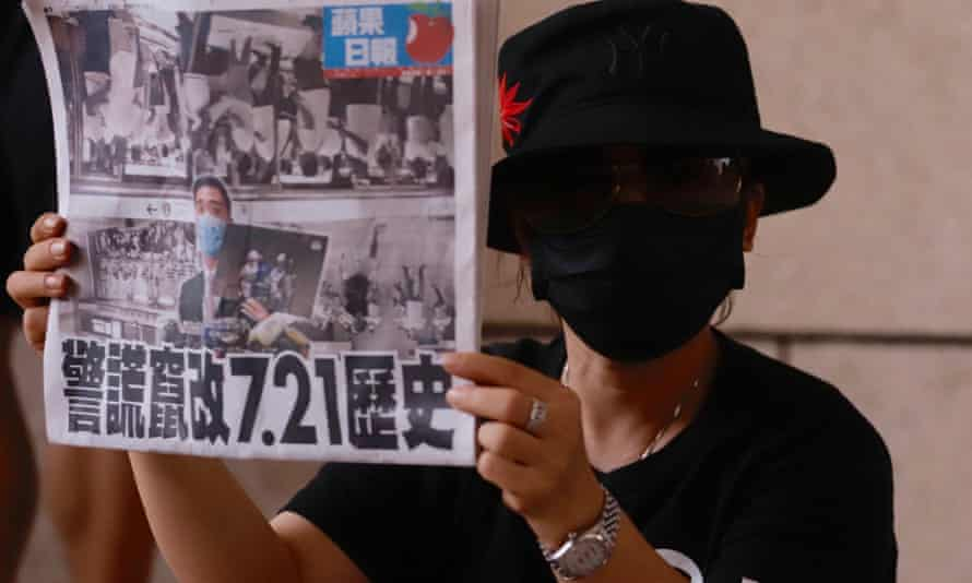 A pro-democracy supporter displaying a copy of Apple Daily's front page last week