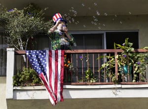 A man blows bubbles from an apartment patio after Joe Biden defeated Donald Trump Saturday in Los Angeles.