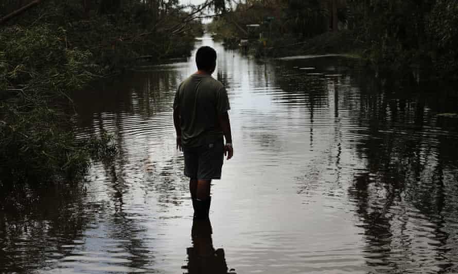 A man walks through a flooded street in Naples, Florida.