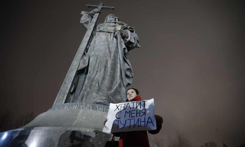 """A protester holds a poster that reads: """"Enough Putin for me"""" as she stages a one-woman protest in front of the monument of Prince Vladimir next to the Kremlin in Moscow."""
