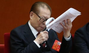 Former Chinese president Jiang Zemin holds a magnifying glass while reading a document during the opening ceremony of the party congress