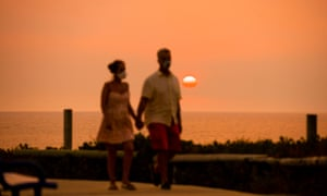 A man and woman are seen along the Cottesloe foreshore as the sun sets with smoke haze