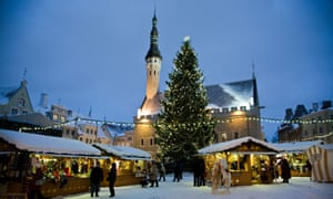 Wooden hut stalls in Tallinn's Town Hall Square with a large xmas tree and the church hall with spire in the background, a bright blue sky and snow on the roofs