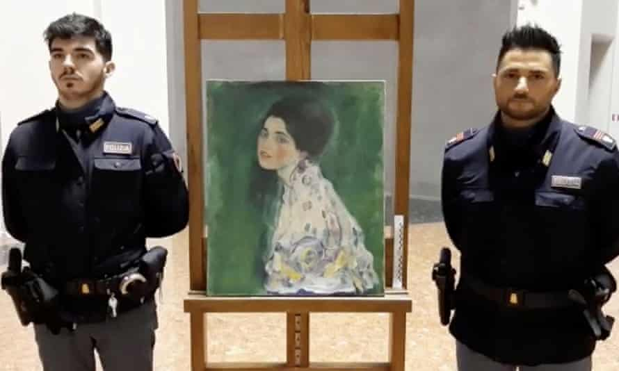 Italian police stand next to what they say could be the Portrait of a Lady painting, by the Austrian artist Gustav Klimt, which was stolen in 1997.