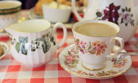 Traditional English afternoon tea with flowery china teacup and saucer on a red and white table cloth in a cafe