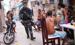 A Brazilian military police officer patrols the unpacified Complexo da Mare favela complex in Rio de Janeiro in 2014.