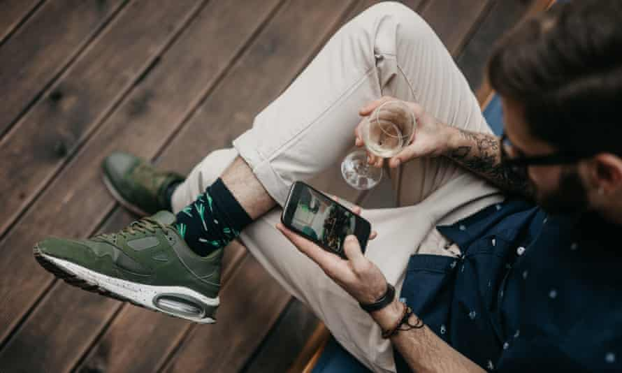 Young man relaxing in a garden with wine and phone