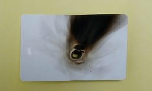 Burnt identity card. Photograph by Martin Godwin.