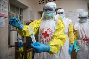 The Red Cross is concentrating on helping give safe and dignified burials to those who have died of Ebola. The first step is negotiating with the family so that they understand and give their permission for what will happen during the burial. Then volunteer safe burial teams wearing protective clothing take the dead from their homes. The bodies are wrapped in a protective covering as well so that neither the burial team nor the family will be infected with Ebola.