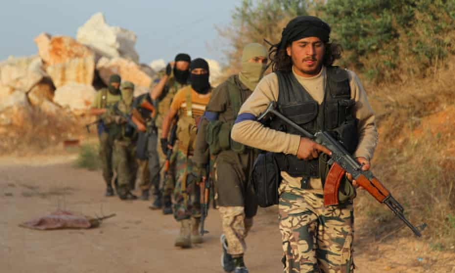 Jabhat al-Nusra fighters carry assault rifles as they move towards their positions during an offensive to take Ariha, Syria, in May 2015