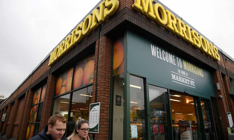 Shoppers walk past a branch of Morrisons in west London.