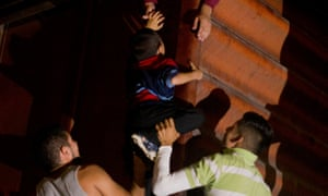 A young boy is hoisted to the top of a boxcar, as Central Americans board a northbound freight train in Arriaga, Chiapas state, Mexico, in 2014.