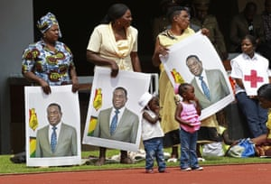 Women hold portraits of Mnangagwa at his inauguration ceremony