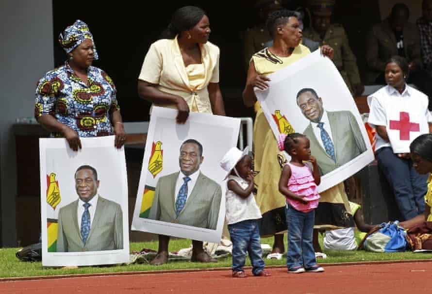 Women hold portraits of Mnangagwa at his inauguration ceremony