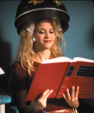 Reese Witherspoon with her hair in a beauty salon dryer reading a book for an exam