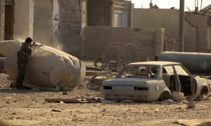 A member of the SDF shoots to detonate a mine.