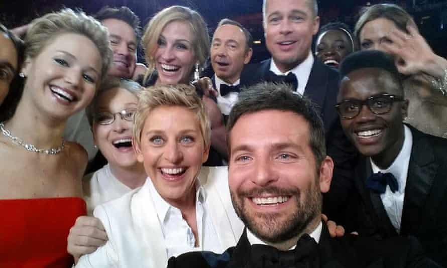 A selfie of about a dozen Hollywood stars crowding in to be included in the shot and smiling, with Bradley Cooper and Ellen DeGeneres closest to the camera