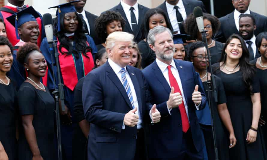 Donald Trump poses with Jerry Falwell Jr in front of a choir during commencement ceremonies in Lynchburg, Virginia, on 13 May 2017.