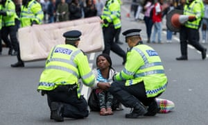 Police with a protester demanding justice after the death of Rashan Charles, London, July 2017