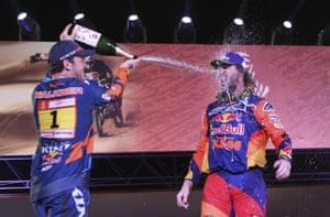 Matthias Walkner who took second place on his KTM motorbike, left, sprays sparkling wine on winner Toby Price.