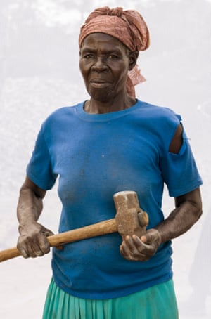 Dan Nelken - From the series HeadStrong: The Women of Rural Uganda: The Quarry Workers December 2019  Olga: Age 74. Working in quarry for 28 years.Israel-born American photographer Dan Nelken created a series of portraits of working women in rural Uganda over three years. As a foreigner, Nelken developed a mutual trust with the workers, who facilitated his access to the quarry, and partnered with Ugandan author Beatrice Lamwaka to transcribe each woman's narrative. Here, quarry worker Olga is posed against a mosquito netting backdrop that obscures the background and separates her physically and metaphorically from her surrounding environment. With this formal portrait, Nelkin aimed to portray Olga as a 'powerful, proud, hard-working and resilient' woman.