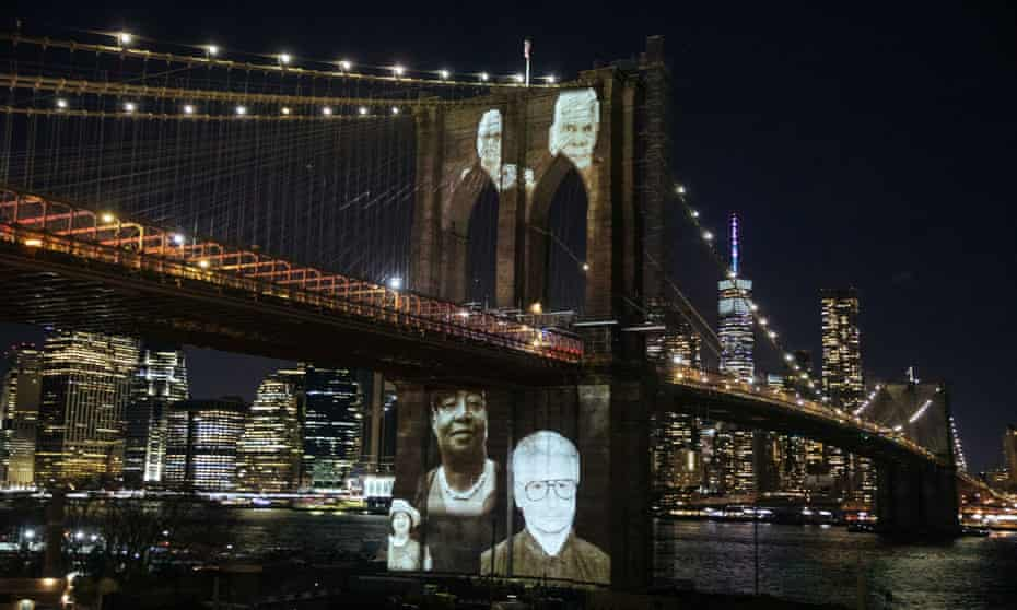 The faces of Brooklyn residents who died from Covid are remembered with photographs projected on to Brooklyn Bridge, New York on 14 March.