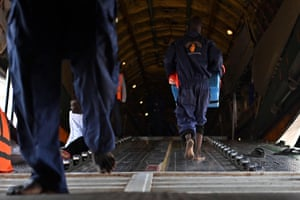 Porters transfer containers with supplementary food rations onto a World Food Programme (WFP) cargo plane at Juba airport