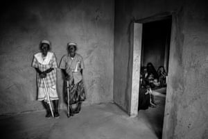 Men and women displaced by conflict wait in separate rooms at a mobile medical clinic in the suburb of Enma