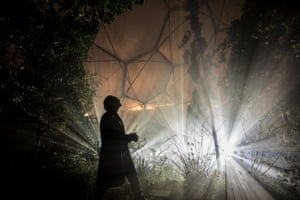 A man looks at the illuminated plants inside the Mediterranean biome