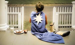 A child dressed as a superhero takes a break