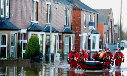 Rescue workers helping residents to safety in Carlisle after heavy rain from Storm Desmond in 2016.