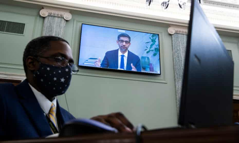 Sundar Pichai, CEO of Google, appears on a monitor behind a stenographer as he testifies remotely during the Senate committee hearing in October 2020.