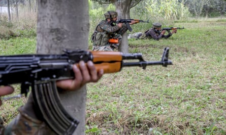 Indian army soldiers take position in an orchard near the site of gunbattle in Pulwama on Saturday.
