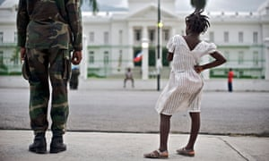 A young girl stands next to a UN soldier in front of the National Palace in Port-au-Prince, Haiti