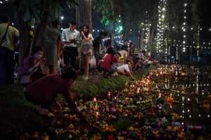 People place krathongs, or floating baskets, in a pond to mark the annual Loy Krathong festival in Bangkok, Thailand.