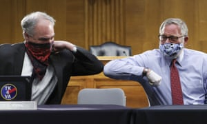 Democratic Senator Tim Kaine (left) and Republican Senator Richard Burr greet each other with an elbow bump before the Senate health committee hearing.