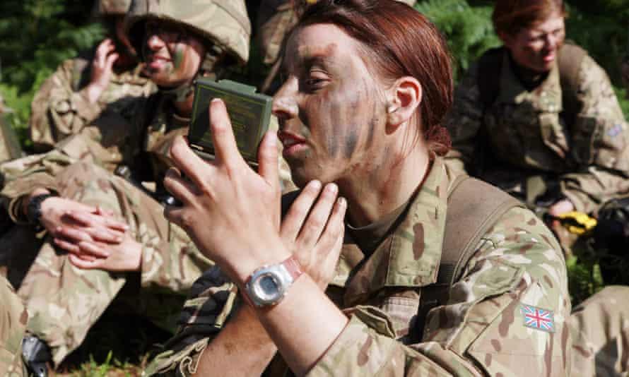 Female recruit at Sandhurst applies camouflage paint.