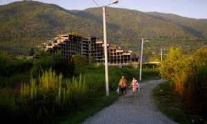 A father and daughter walk to the beach at Gagra.