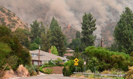 A fire burns on hillsides behind homes in Arcadia, California.