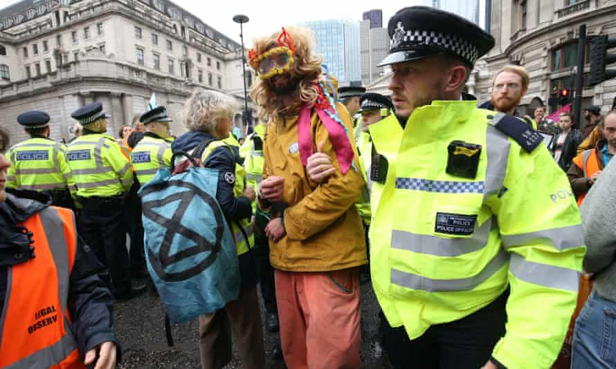 A protester is led away by police as others block the road outside Mansion House in the City of London.