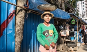 A worker carries building material on her head in central Yangon.